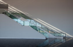 Escalera móvil de cristal con el rayo de sol Fotos de archivo libres de regalías