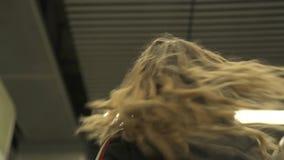 Escalera móvil de la chica joven en metro modernsubway de la estación de m Mujer que mueve encendido la escalera móvil dentro del almacen de metraje de vídeo