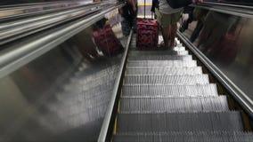 Escalera móvil de Ridign con la gente y el equipaje