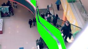 Escalera móvil en alameda de compras con el espacio de publicidad verde de pantalla Muchedumbres de gente en la escalera móvil Ti almacen de video