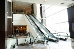 Escalera móvil en el edificio moderno Fotos de archivo