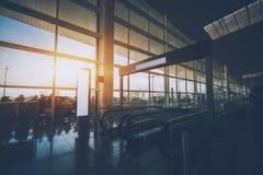Escalera móvil que se mueve abajo en pasillo del terminal de aeropuerto Foto de archivo