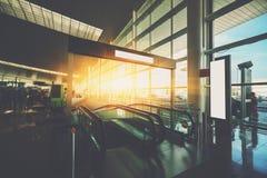 Escalera móvil que se mueve abajo en pasillo del terminal de aeropuerto Imagenes de archivo