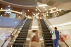 Escalera móvil vacía borrosa en alameda de compras Imagen de archivo libre de regalías