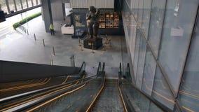 Escalera móvil y la escultura en OUE en el centro de la ciudad metrajes