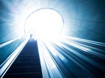Escalera móvil y luz en el extremo Fotografía de archivo libre de regalías