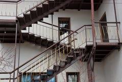 Escalera marrón grande en una pared constructiva gris con ventanas y una puerta imagenes de archivo