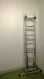 Escalera moderna del hierro que se inclina contra una pared blanca en la condición montada durante la reparación en el apartament imágenes de archivo libres de regalías