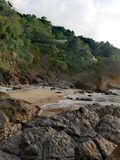 Escalera pedregosa que lleva de la playa rocosa arenosa para poner verde las colinas deliciosas de Mindoro imagen de archivo