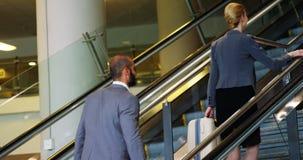 Escalera que sube del hombre de negocios y de la mujer con equipaje almacen de video