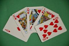 Escalera real avivada del póker de la mano hacia fuera que gana en la tabla verde de la bayeta Foto de archivo libre de regalías