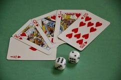 Escalera real roja y dados del póker de los ganadores de los corazones en etiqueta verde de la bayeta Foto de archivo libre de regalías