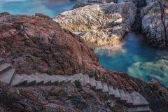 Escalera rocosa, roca aclarada y mar de la esmeralda foto de archivo libre de regalías