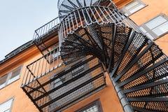 Escalera trasera del espiral del metal en la pared roja Imágenes de archivo libres de regalías