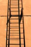 Escalera vieja del metal y pared anaranjada Fotografía de archivo