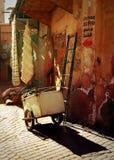 Escalera y carro contra una pared en Marrakesh en la puesta del sol Imágenes de archivo libres de regalías