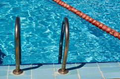 Escalera y manija de las escaleras abajo a la piscina Fotos de archivo