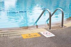 Escalera y señal de peligro en la piscina del swimmimg Fotos de archivo