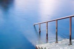 Escaleras abajo al agua azul Fotos de archivo