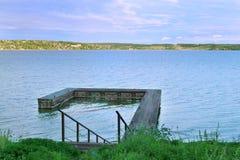 Escaleras abajo al embarcadero de madera en el gran río Kama por la tarde Fotografía de archivo