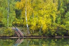 Escaleras al agua en la orilla del río del otoño Foto de archivo libre de regalías