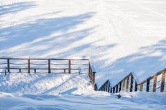Escaleras al aire libre llenas de hielo y de nieve Las escaleras de madera en la montaña que emigra la ruta en invierno que tiene fotografía de archivo libre de regalías