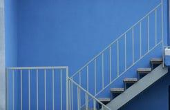 Escaleras con el pasamano de la seguridad contra la pared azul Fotos de archivo