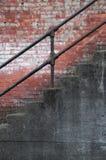 Escaleras con el pasamano del hierro y la pared de ladrillo vieja Imagen de archivo libre de regalías