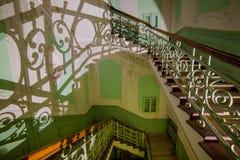 Escaleras con las verjas elegantes en una casa abandonada vieja, molde fotografía de archivo