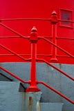 Escaleras concretas con el pasamano rojo Fotos de archivo libres de regalías