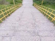 Escaleras concretas con las escaleras amarillas de la barandilla que van abajo Imagen de archivo