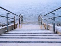 Escaleras concretas que llevan en el agua Imagenes de archivo