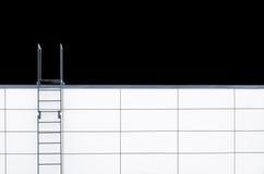 Escaleras de la emergencia del metal en la pared blanca Imagen de archivo