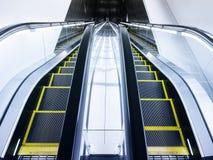 Escaleras de la escalera móvil hacia arriba y hacia abajo en interior moderno del edificio Imagen de archivo