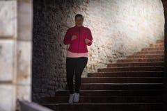 Escaleras de la ropa de deportes y del funcionamiento de la muchacha que llevan abajo en la fortaleza de la ciudad Fotografía de archivo libre de regalías