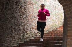 Escaleras de la ropa de deportes y del funcionamiento de la muchacha que llevan abajo en la fortaleza de la ciudad Fotos de archivo