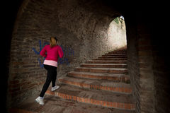 Escaleras de la ropa de deportes y del funcionamiento de la muchacha que llevan abajo en la fortaleza de la ciudad Imágenes de archivo libres de regalías