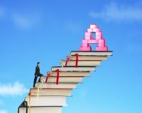 Escaleras de los libros del hombre de negocios que suben hacia bloques de la forma del alfabeto A Fotos de archivo