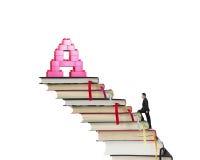 Escaleras de los libros del hombre de negocios que suben hacia bloques de la forma del alfabeto A Foto de archivo libre de regalías