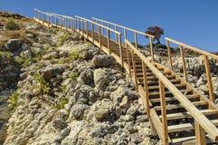 Escaleras de madera a varar en la orilla rocosa fotos de archivo