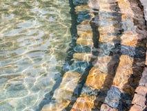 Escaleras de piedra abajo en el agua Imágenes de archivo libres de regalías