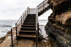 Escaleras del acceso del océano de la persona que practica surf de los acantilados de la puesta del sol en San Diego fotografía de archivo