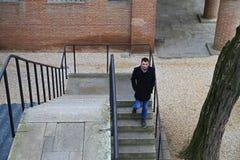 Escaleras descendentes blancas del hombre joven, sonriendo Fotografía de archivo