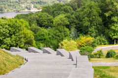 Escaleras grises de la piedra del granito que dan vuelta suavemente a la izquierda en un parque de la ciudad Bosque y río en el f Imágenes de archivo libres de regalías