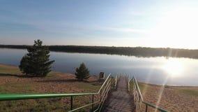 Escaleras a la puesta del sol de la orilla sobre el río almacen de video