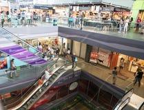 Escaleras móviles abajo de varios pisos, tiendas y personas en tienda al por menor Fotografía de archivo libre de regalías