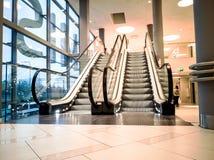 Escaleras móviles en las compras modernas imágenes de archivo libres de regalías