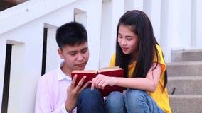 Escaleras que se sientan del estudiante asiático en el lugar al aire libre Junte a la gente que usa el libro metrajes