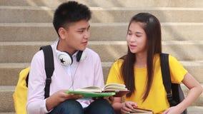 Escaleras que se sientan del estudiante asiático en el lugar al aire libre Junte a la gente que usa el libro almacen de metraje de vídeo