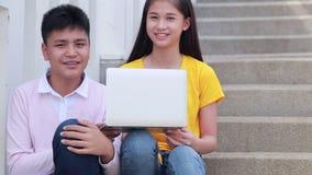Escaleras que se sientan del estudiante asiático en el lugar al aire libre Junte a la gente que usa el libro y el ordenador portá almacen de metraje de vídeo